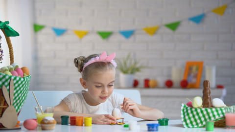 Adorable little girl decorating Easter eggs with colorful paint, talented child Footage