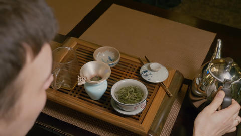 Tea master pours hot water from kettle to gaiwan with green tea at wooden table Live Action