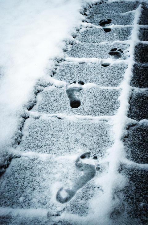footprints feet on the snowy sidewalk Fotografía