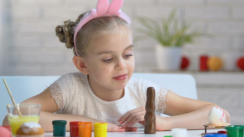 Adorable girl playing with chocolate bunny and smiling into camera, childhood Live Action