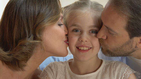 Caring parents tenderly kissing on cheeks their little daughter, love and pride Footage