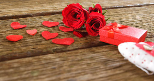 Red roses, gift box and heart shapes on the wooden surface 4k Live Action