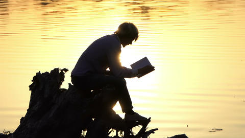 Creative man reads a book to write an article at a lake Live Action