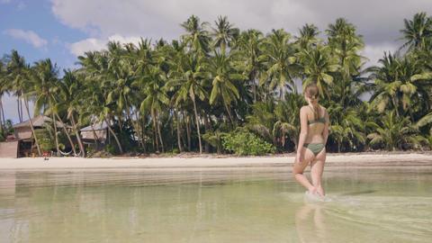 Beautiful woman in bikini walking on sea beach ant falling in fresh water at hot Footage