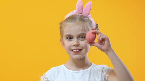 Adorable child having fun holding colored egg near eye, perfect Easter mood Footage