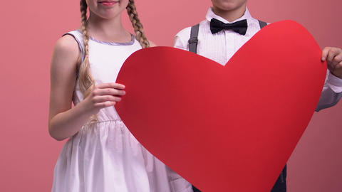 Kids holding big red heart and smiling, happy childhood, love and care concept Footage