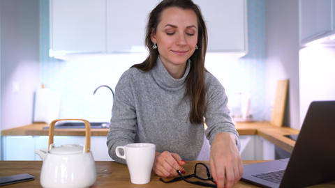 Caucasian woman having breakfast in the kitchen and using a laptop Footage
