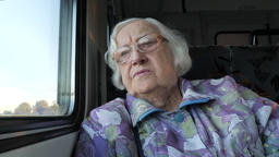 Elderly woman looks through the window in a train Live Action