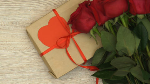 Person putting love letter by roses and gift box, Saint Valentines day surprise Live Action