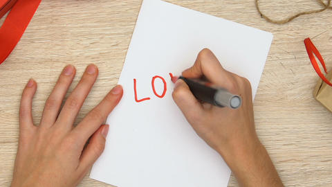 Woman writing love word on paper, romantic relationship between man and woman Footage
