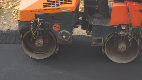 Road roller rolls new asphalt Live Action