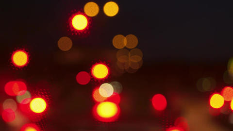 Blurry bokeh shot of red traffic lights turning to green in town traffic Live Action