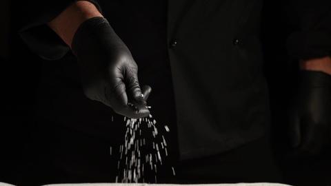 black latex gloved hand sprinkles white coarse salt Archivo
