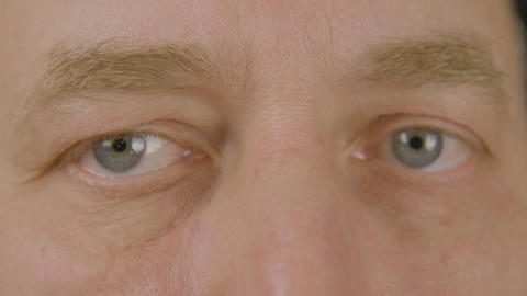 Man with opened eyes looking and blinking front camera close up. Macro male eyes Live Action