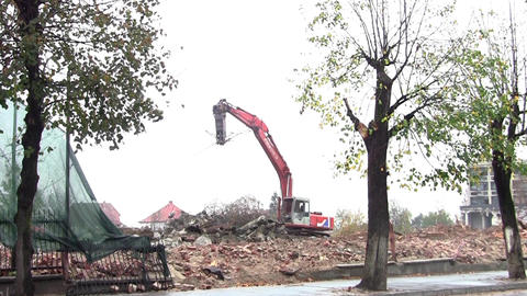 Excavator going on a field where a building has been demolished and keeping his Footage