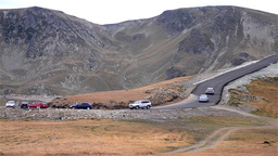 Cars which run column on a paved road in a mountain area 99 Footage
