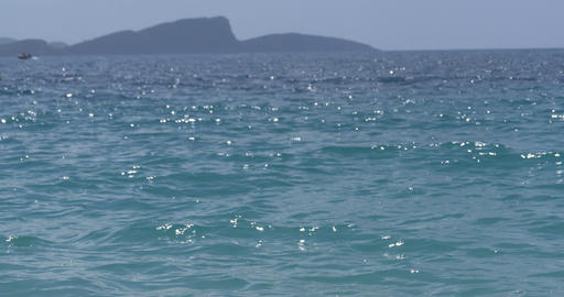 Speed boat moving offshore going to the mountain that is seen in the distance 93 Footage