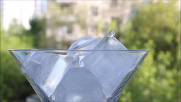 Ice cubes appear one after another in a martini glass Footage