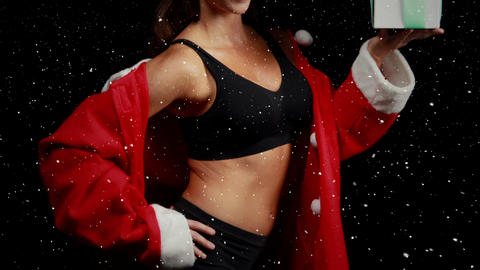 Video composition with falling snow over happy girl in santas suit while holding gift box Animation