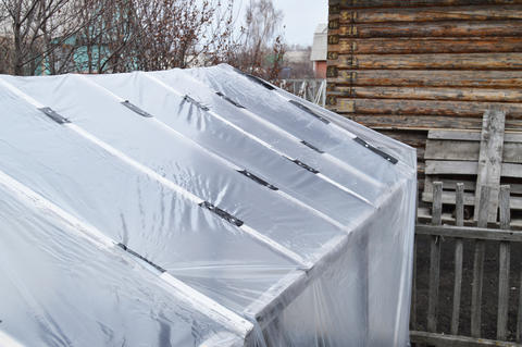 Greenhouse for growing vegetables in the garden. Covered with polyethylene film フォト