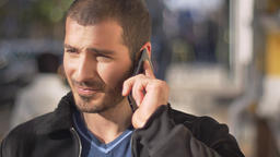 Portrait of young caucasian man happily talking on cellphone with blurred Footage