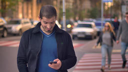 Portrait of caucasian man standing on cross-walk and watching into smartphone Footage