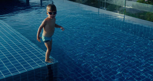Funny boy dives into swimming pool Footage