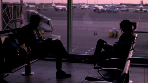 Silhouettes of people sitting in waiting room, passing time before flight Footage
