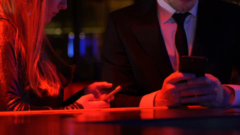 Indifferent young couple spending time with smartphones in bar, gadget addiction Live Action