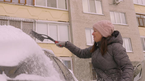 Smiling woman driver cleaning car from snow at parking lot in winter day Footage