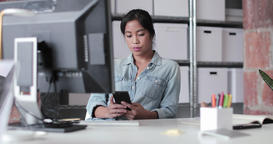 Young adult female working in an office looking at a smartphone Live Action