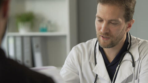 Attentive male doctor reading medical test result and prescribing vitamins Live Action