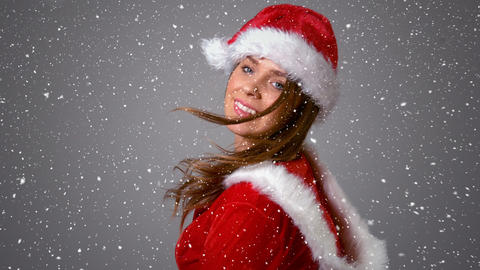 Video composition with falling snow over girl in santas suit turning around Animation