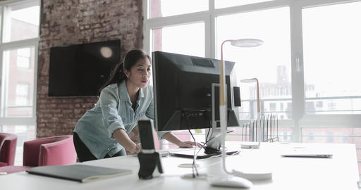 Young adult female working on a desktop computer then looking at the view Footage