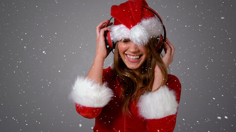 Video composition with falling snow over happy girl in santas suit dancing Animation
