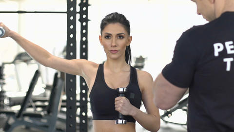 Sportive girl exercising with dumbbell, personal trainer motivating, support Live Action