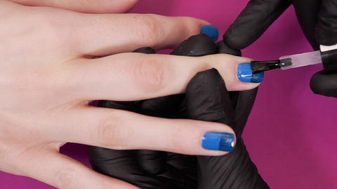Manicurist paints client's nails with transparent nail polish on the pink ビデオ