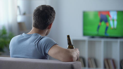 Male supporter watching football drinking beer, disappointed with tie in match Footage
