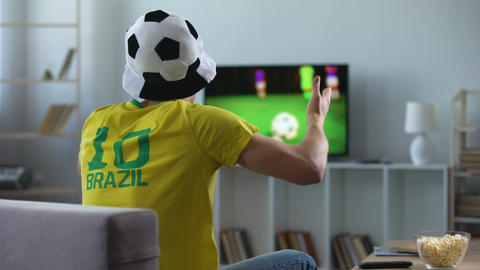 Brazilian team supporter actively cheering favourite football team, match on tv Live Action