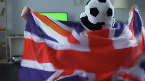 Man holding Great Britain flag, supporter watching football game on tv at home Live Action