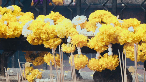 Candle smoke and yellow flowers at temple In Bangkok Footage