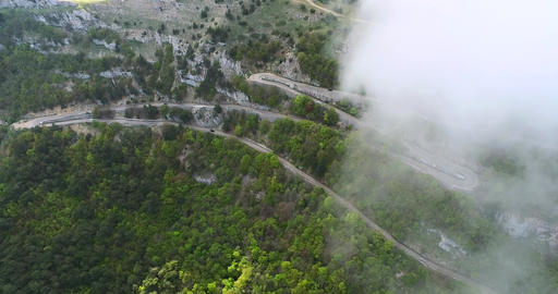 Flying In Clouds Above Serpentine Road Footage
