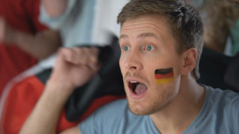 Emotional German football fan chanting and supporting team, watching game on tv Footage