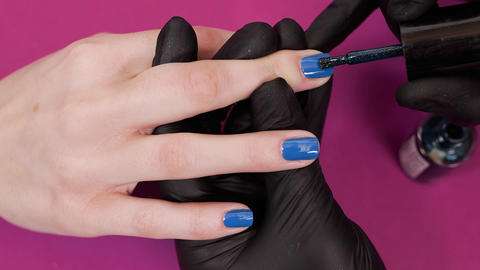 Manicurist paints client's nails with blue tint nail polish on the red ビデオ