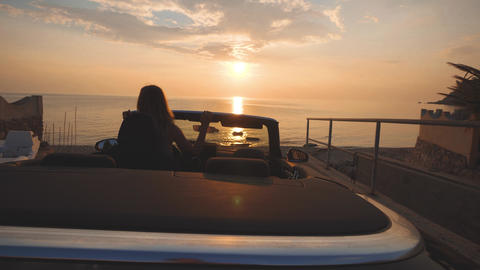 Girl dances on driver place in cabriolet car. Gentle colors of sunset over sea GIF