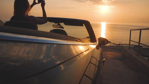 Girl takes a picture of sunset and ocean by smartphone from cabriolet car Footage