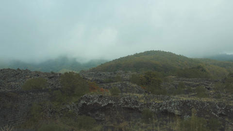 Moving in car by rocky slopes. Mountain tops covered with gray clouds. Side Footage