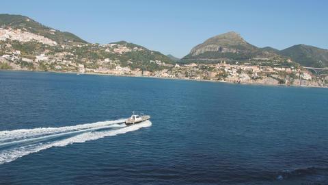 Pilot boat floats towards coastal city. Blue sea and hilly shore on sunny day Live Action
