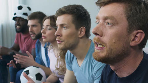Group of fans watching football on television at home, convenient entertainment Live Action