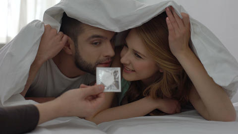 Hand holding condom in plastic, offering safe intimate relations to young couple Footage